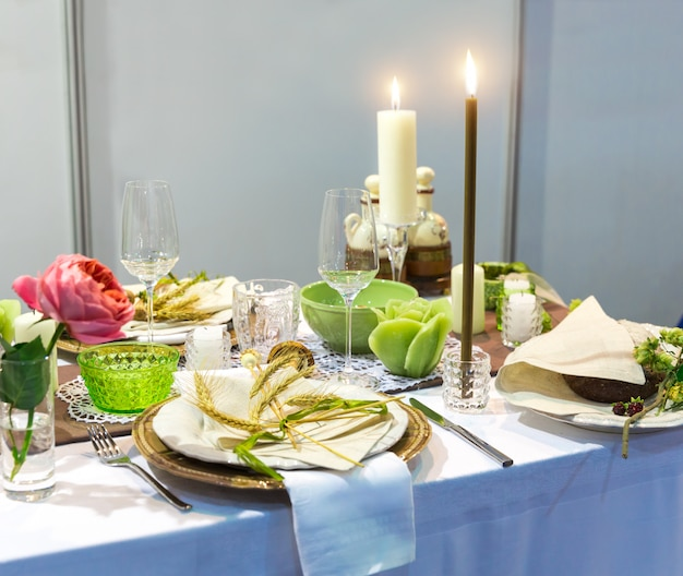 Romantic dinner, table with decoration, nobody. candles, plates with ears of wheat decor