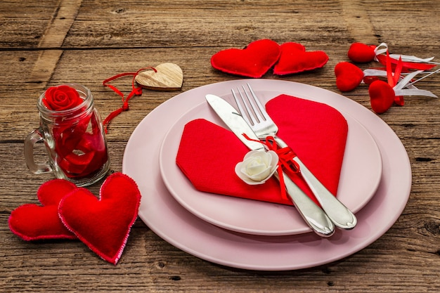 Romantic dinner table with plates and heart shape napkin