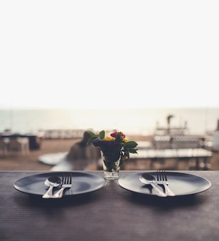 Romantic dinner with beautiful view on the beach, plate, spoons and forks on the table