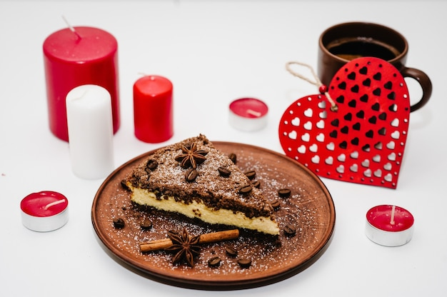 A romantic dinner with candles for valentine's day. cake with coffee. decorated red hearts on a white wooden surface.