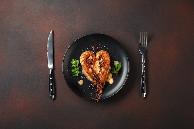 Romantic dinner with heart-shaped shrimps and wine on a brown background. top view with copy space