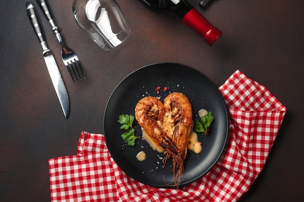 Romantic dinner with heart-shaped shrimps and wine on brown