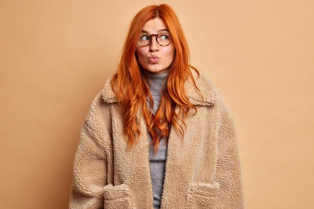낭만적 인 꿈꾸는 여자는 입술을 접고 멀리 보이는 모피 코트를 입은 즐거운 무언가가 광학 안경을 착용한다고 상상합니다.