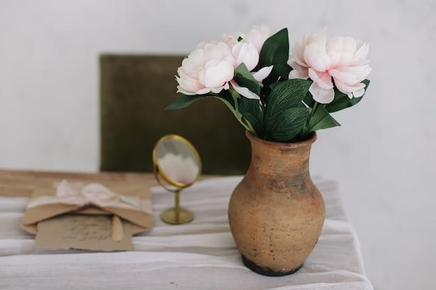 Романтический туалетный столик с букетом пионов в вазе и зеркалом