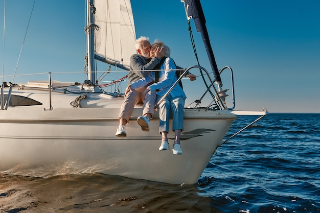 Romantic elderly couple embracing and kissing while relaxing on sail boat or yacht deck floating in