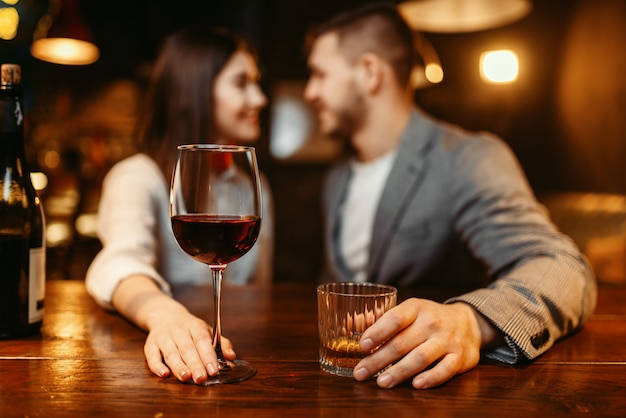 Romantic evening in bar, love couple at wooden counter. lovers leisures in pub, husband and wife relaxing together in nightclub
