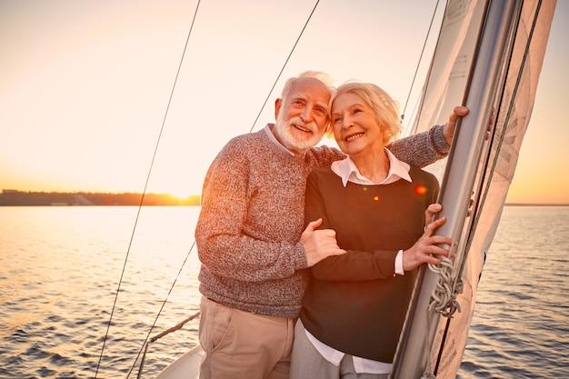ボートに乗ってロマンチックな夜幸せな年配のカップルが立っている間抱き締めて素晴らしい夕日を楽しんでいます