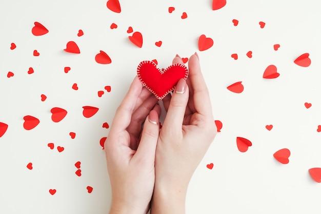 Концепция романтических чувств. вид сверху на руки леди, держа красное сердце из фетра ручной работы на белом фоне любви.