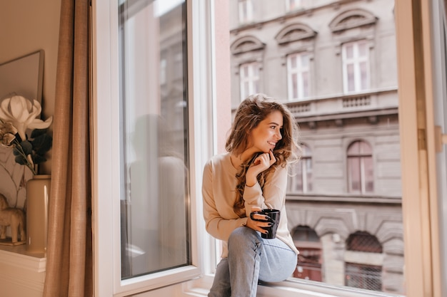 Romantic female model in good mood looking at street, sitting on sill