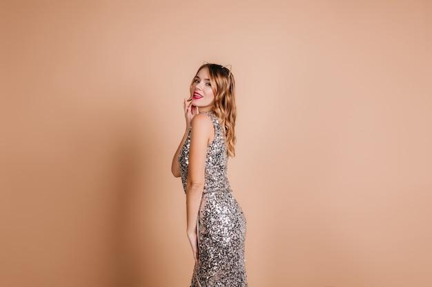 창백한 피부가 생일 파티에서 스파클 드레스를 입고 포즈를 취하는 로맨틱 여성 모델