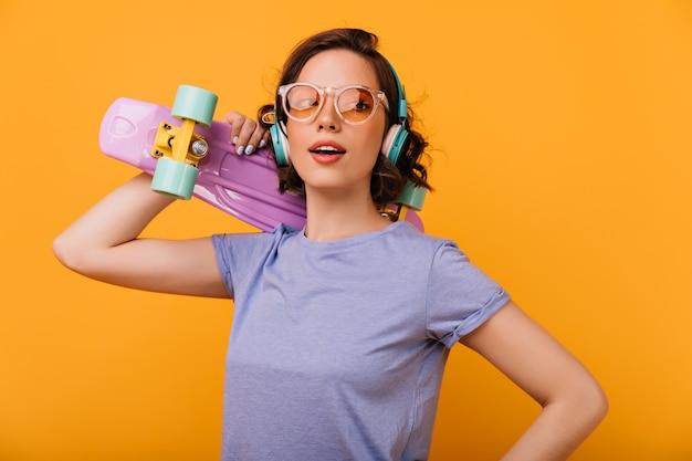 트렌디 한 안경 포즈에 낭만적 인 여성 스케이트 보더. 고립 된 보라색 longboard와 유행 백인 여자의 사진.