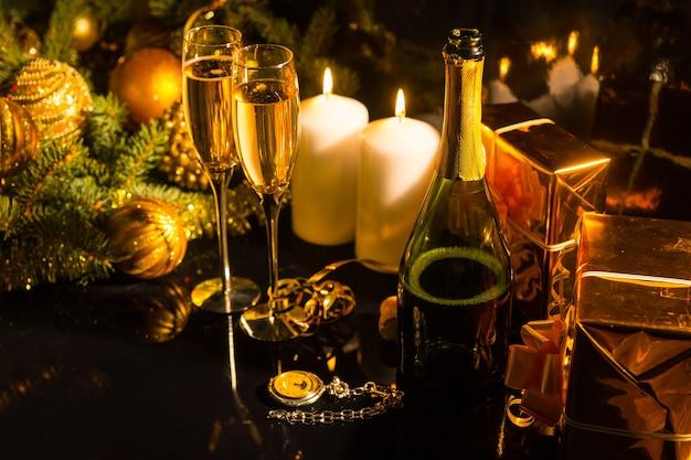白い燃えるろうそく、装飾された松の枝、金色の光沢のある紙で包まれたギフトボックス、フルートグラス、クリスマスや新年を祝うためのシャンパンを備えたロマンチックなお祝いのアレンジメント
