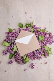 ロマンチックな花の構成は紫色の背景にライラックの花とフレームをモックアップします。