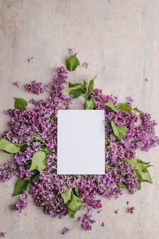 Romantic flowers composition mock up frame with lilac flowers on purple background
