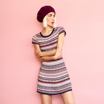 Romantic french style stylish girl in a beret and dress burgundy color