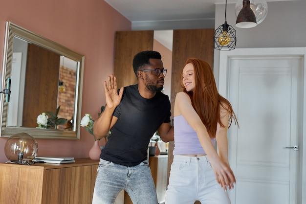 家で踊るロマンチックな面白いカップル、魅力的な赤毛とハンサムな男
