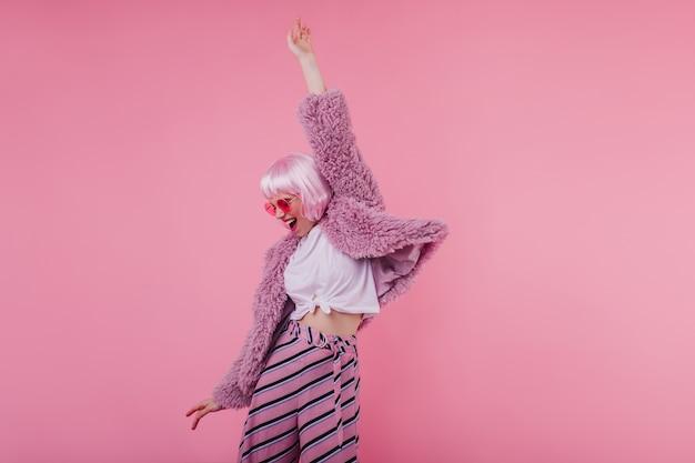 Ragazza romantica in occhiali da sole luminosi e peruke che balla sulla parete rosa. splendido modello femminile in pantaloni a righe e giacca di pelliccia che ride