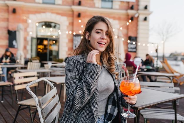 Ragazza romantica in abiti casual agghiacciante nella caffetteria nel fine settimana autunnale e degustazione di cocktail