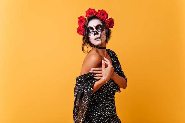 Romantic girl gently holds falling dress. lady with make-up in form of skull for carnival mysteriously looks away.
