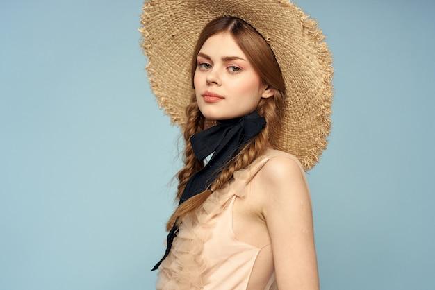 灰色の背景とベージュのサンドレス黒リボン感情モデルの麦わら帽子のロマンチックな女の子。
