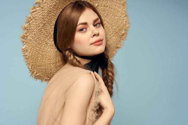 Романтичная девушка в соломенной шляпе на сером