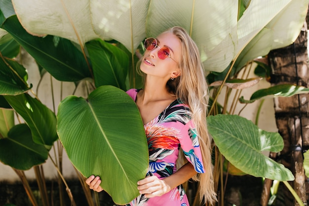 Романтичная девушка в ярком стильном наряде наслаждается фотосессией на фоне природы.
