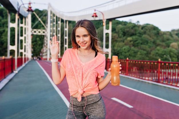 スタジアムで楽しんでいるピンクのt-shortのロマンチックな女の子。燃えがらトラックで笑っている水のボトルを持つ愛らしい若い女性。