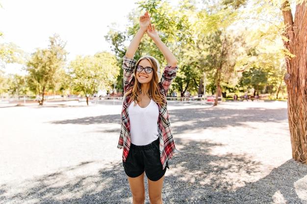 자연에 포즈를 취하는 빨간 셔츠에 로맨틱 소녀. 여름날을 즐기는 슬림 유럽 여성 모델.