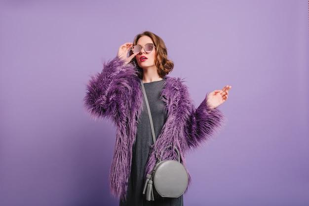 トレンディなサングラスを通して見ている柔らかいふわふわのジャケットのロマンチックな女の子