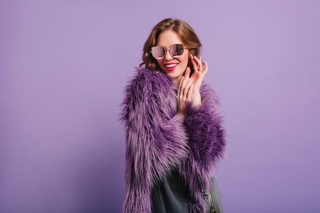 Романтичная девушка в стильном фиолетовом наряде позирует с застенчивой улыбкой в студии