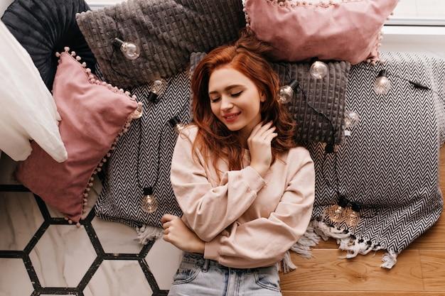 灰色の枕の上に横たわっているロマンチックな女の子。居心地の良い部屋でポーズをとる陽気な生姜の女性の屋内写真。