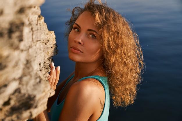 水の背景に岩の近くのロマンチックな女の子。