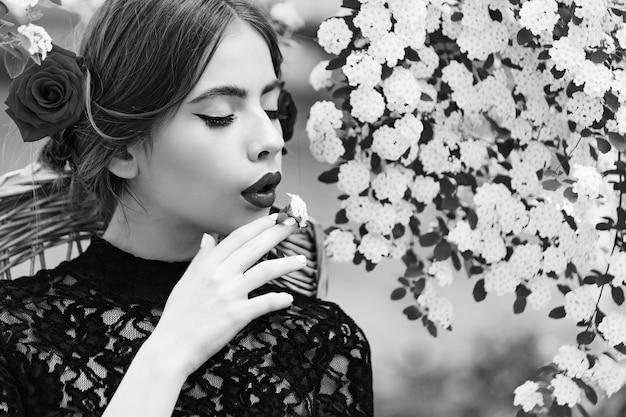 로맨틱 소녀 또는 입에 흰 꽃과 젊은 여자. 봄과 여름. 자연의 아름다움.