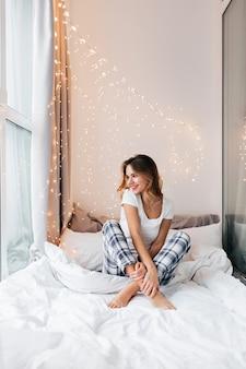 Романтичная девушка позирует на лоджии, украшенной огнями. фотография в помещении улыбающейся любезной дамы, наслаждающейся выходными в своей квартире.