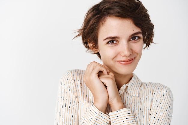 Романтичная девушка, нежно улыбаясь от восхищения, стоит в блузке над белой стеной