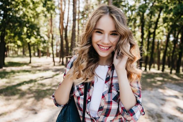 森の中でポーズをしながら電話で話しているロマンチックな女の子。自然の上に立っている陽気な笑顔とデボネアブロンドの女性の屋外写真。