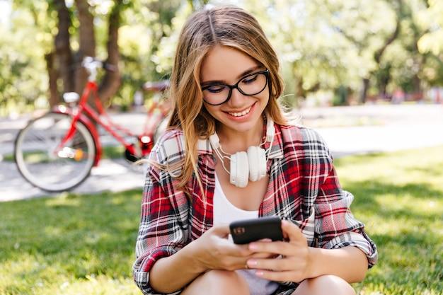 아름 다운 공원에서 휴식하는 동안 로맨틱 소녀 문자 메시지. 스마트 폰으로 잔디에 앉아 밝은 금발 여자의 야외 사진.