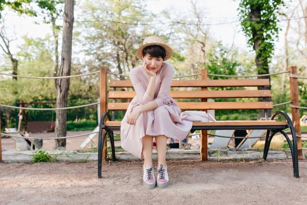 Ragazza romantica che indossa cappello di paglia alla moda che si siede sulla panchina del parco puntellando il viso con la mano e pensando a qualcosa di buono