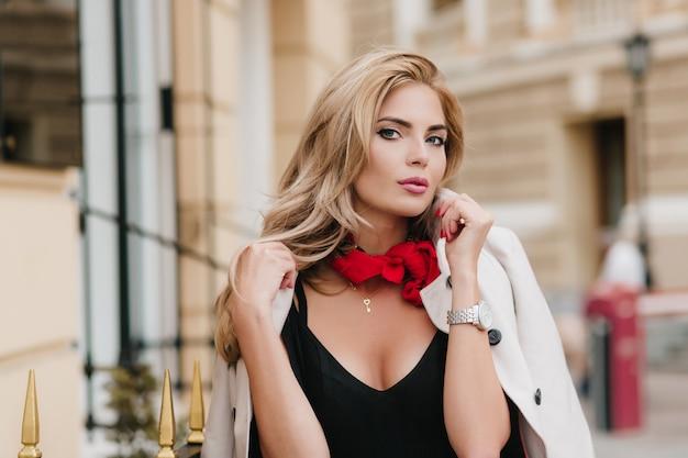 Романтичная девушка в золотом кулоне смотрит с интересом, позируя после прогулки по городу