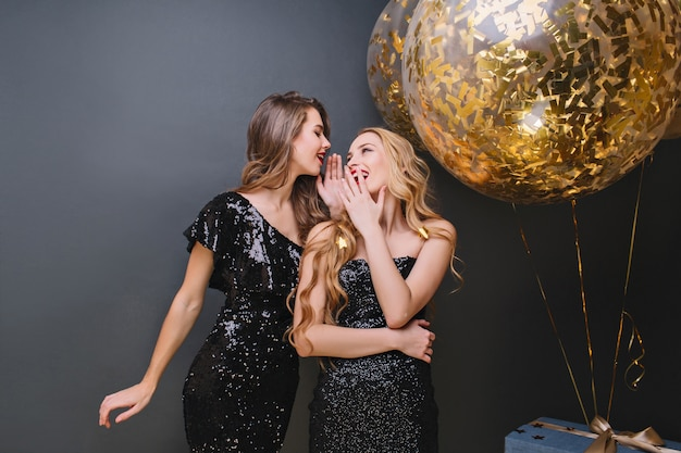 Romantic girl with blonde long hair smiling and covering mouth with hand. charming ladies in sparkle dresses having fun together during event.