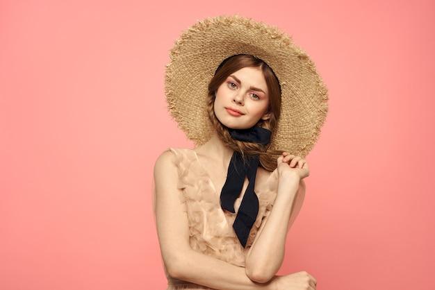 おさげと麦わら帽子のロマンチックな女の子の笑顔のロマンスピンクの壁のコピースペース。