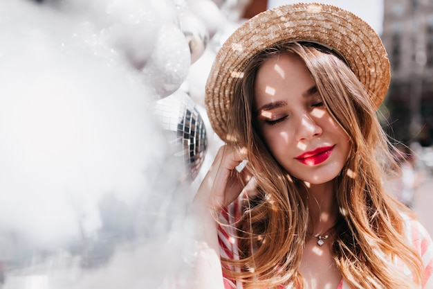 Romantic girl with red lips posing with eyes closed near sparkle ball. outdoor shot of pensive jocund woman in straw hat.