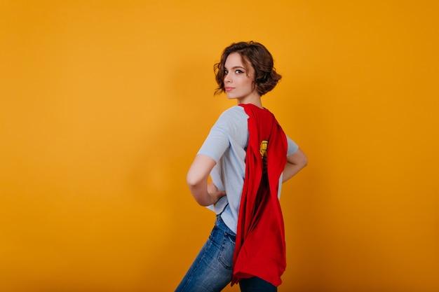 Романтичная девушка с серьезным выражением лица позирует в красном плаще супергероя