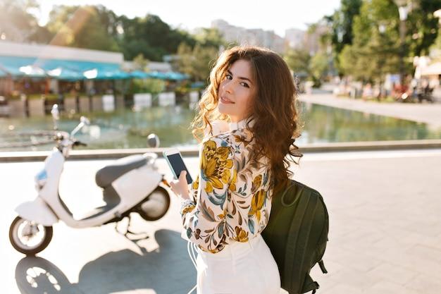 Ragazza romantica con acconciatura alla moda guardando sopra la spalla, in piedi con il telefono in mano davanti alla fontana