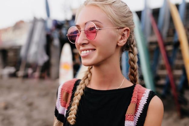 ピンクのサングラスでポーズをとる流行の髪型を持つロマンチックな女の子。天気の良い日を楽しんでいる三つ編みのゴージャスなブロンドの女性の屋外ショット。
