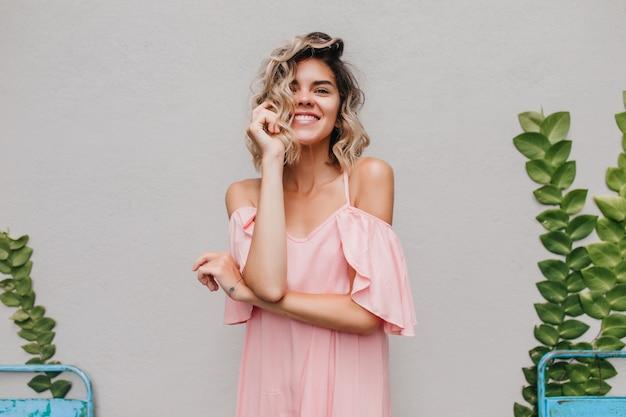 미소로 그녀의 얼굴을 만지고 물결 모양의 머리를 가진 로맨틱 소녀. 녹색 식물 근처에 서있는 화려한 무두 질된 여성 모델의 실내 사진.