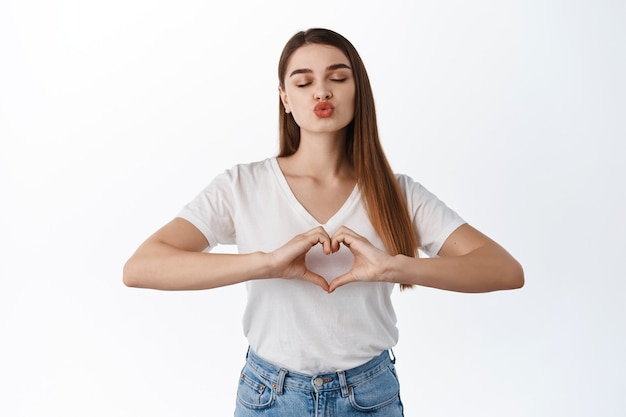 Romantic girlfriend close eyes and kissing, showing kiss puckered lips and heart sign, i love you gesture, like someone, white wall