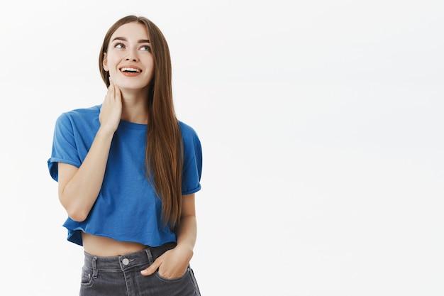 ロマンチックな見栄えの良いヨーロッパの女性のブルネットの青いtシャツで首に優しく触れ、右上隅をじっと見つめると、灰色の壁に官能的な喜びのある笑顔が懐かしい