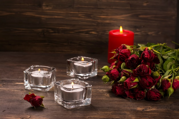 Romantic greeting card: bunch of roses and candles over dark wooden background