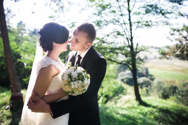 Romantic groom hugging his wife before kissing her